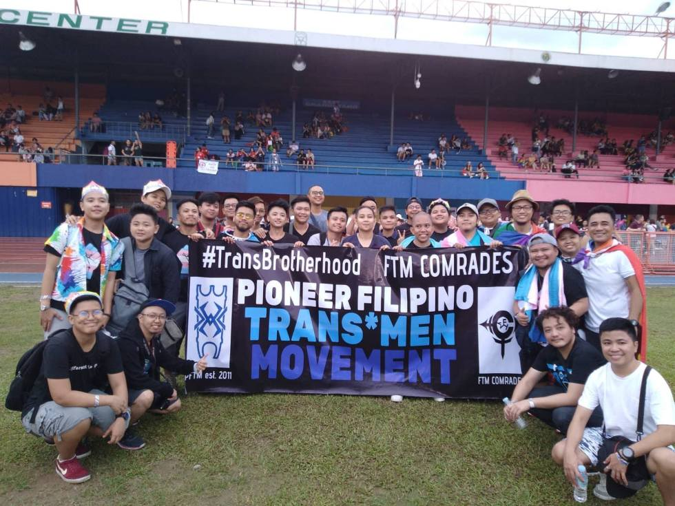 "PFTM members posing by sign at a stadium. Sign reads ""#TransBrotherhood FTM Comrades Pioneer Filipino Trans*Men Movement"""