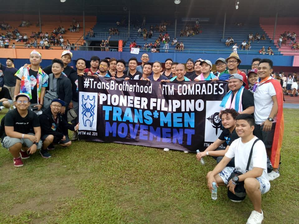 "PFTM members posing by sign. Sign reads ""#TransBrotherhood FTM Comrades Pioneer Filipino Trans*Men Movement"""