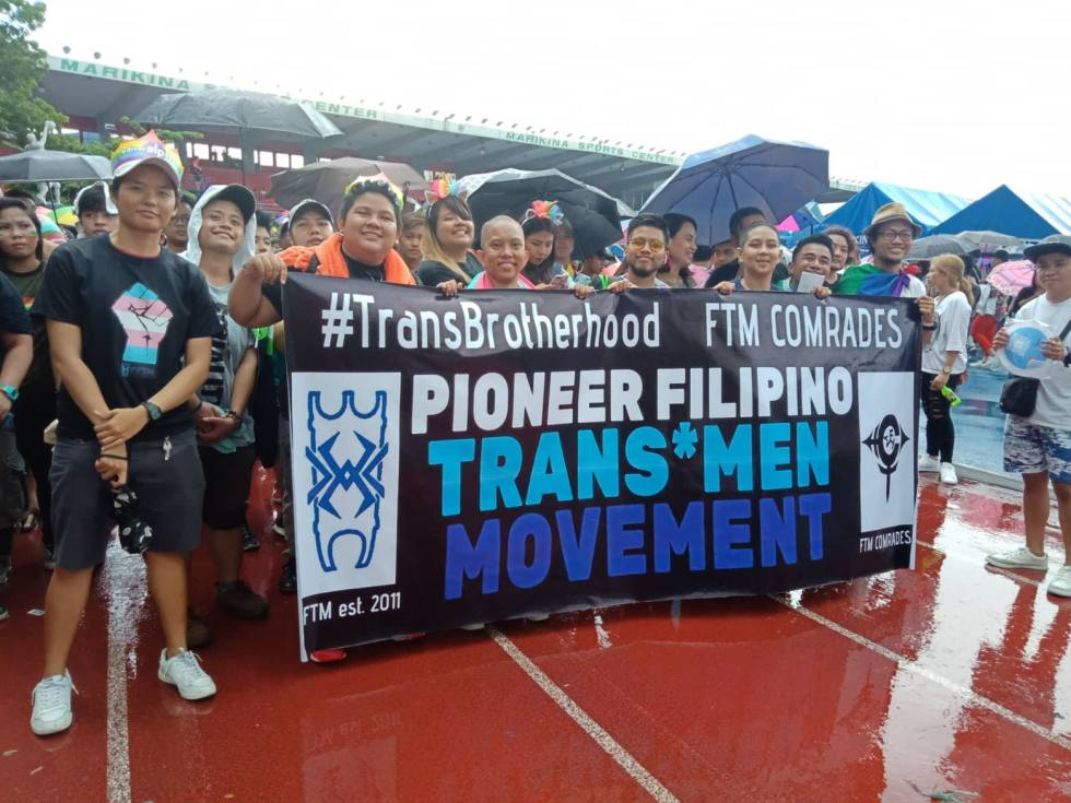 "Pioneer FTM members posing by sign. Sign reads ""#TransBrotherhood FTM Comrades Pioneer Filipino Trans*Men Movement"""